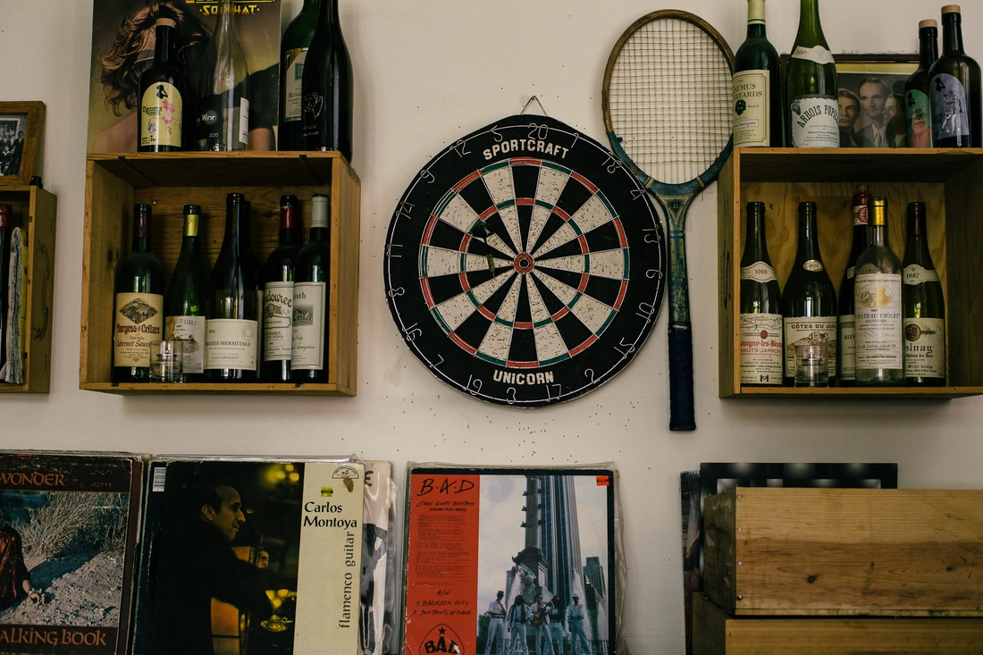 Interior shot of Terroir showing wine bottles, dart board and tennis racket